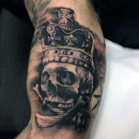 Black and gray style skull with crown tattoo on biceps combined with crossed bones