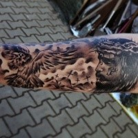 Black and gray style unusual dramatic Jesus portrait tattoo on arm combined with cemetery and crow