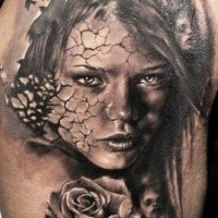 Black and gray style very detailed shoulder tattoo of woman with corrupted face and rose