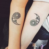 Black and white forearm and side tattoo of Yin Yang symbol parts stylized with ornamental flowers