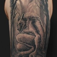 Black and white shoulder tattoo of demonic werewolf with dark forest