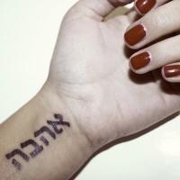 Tatuaje en la muñeca,  inscripción hebrea,  letras gruesas negras