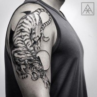 Black ink Asian style shoulder tattoo of tiger with circles