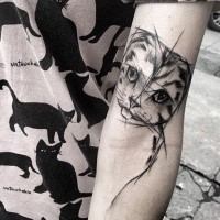 Black ink cat tattoo sketch tattoo painted by Inez Janiak on biceps