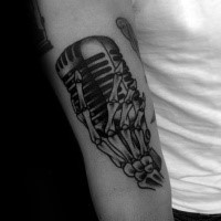 Black ink engraving style biceps tattoo of skeleton hand with vintage microphone