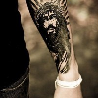 Black ink jesus in a wreath and nimbus forearm tattoo