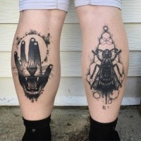 Black ink medium size painted by Michael J Kelly legs tattoo of human hand and bug with lion teeth