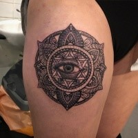Black ink thigh tattoo of mystical eye with flowers