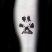 Black ink typical leg tattoo of animal paw print with triangle