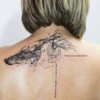 Black ink upper back tattoo of wolf with lettering and ornaments