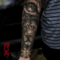 Black lion tattoo on forearm