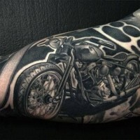 Black motorcycle and brass knuckles arm tattoo