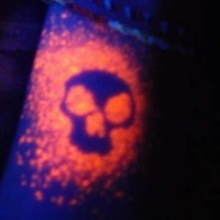 teschio arancione luce nera tatuaggio