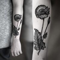 Tattoo mit schwarzem Mohn am Unterarm
