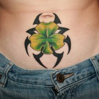 Black tribal with irish clover tattoo on stomach