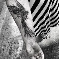 Blackwork style big bird tattoo painted by Inez Janiak on forearm