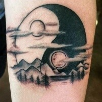 Blackwork style big Yin Yang symbol tattoo on forearm stylized with mountains