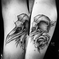 Blackwork style designed by Inez Janiak arm tattoo of bird skull with rose
