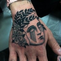 Blackwork style simple looking hand tattoo of woman head with flowers