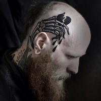 Blackwork style simple looking head tattoo of skeleton hand with broken heart