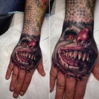 Bloody colored arm tattoo of creepy clown face