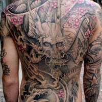 Breathtaking massive half colored Asian dragon with flowers tattoo on whole back
