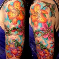 Bright colored lily flowers with hummingbirds, bee and grasshopper upper arm tattoo with blue haze