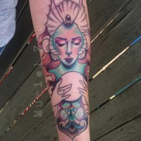 Brilliant designed and colored magical mermaid tattoo on forearm with magic orb