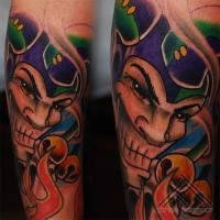 Cartoon style colored arm tattoo of evil Joker