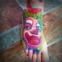 Cartoon style colored foot tattoo of creepy clown face