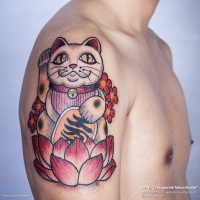 Cartoon style colored shoulder tattoo of typical maneki neko japanese lucky cat with lotus flower and symbols