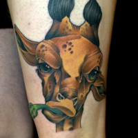 Cartoon style colored thigh tattoo of giraffe eating plant