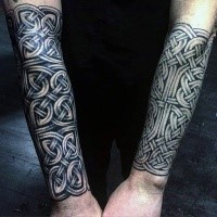 Celtic style typical looking black ink forearm tattoo of various knots