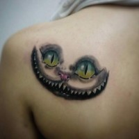 Cheshire cat's smile and look colored fairy tale tattoo on lady's shoulder blade