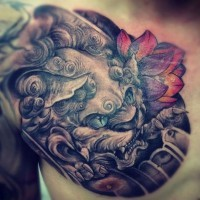 Chinese lion head with red lotus tattoo on shoulder