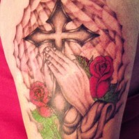 stile cristiano dipinto mani pregando con crocefisso e fiori tatuaggio su spalla