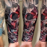 Colored forearm tattoo of mystical red skull