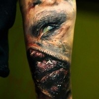 Colored horror style creepy looking arm tattoo of monster face