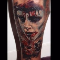 Colored horror style creepy looking leg tattoo of human mask with blood
