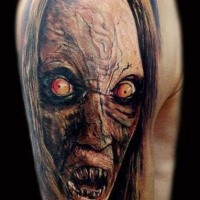 Colored horror style creepy looking shoulder tattoo of monster face