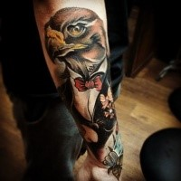Colored illustrative style arm tattoo of eagle with tox and flowers
