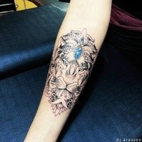 Colored illustrative style forearm tattoo of lion with blue diamond