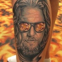 Colored leg tattoo of man portrait in sun glasses