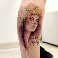 Colored leg tattoo of woman face with tree and lettering