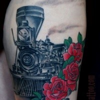 Colored memorial thigh tattoo of steam train with roses