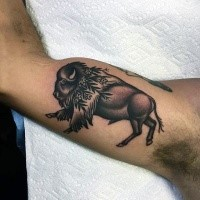 Colored small biceps tattoo of running bull with flowers