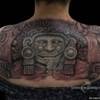 Colored typical looking upper back tattoo of ancient stone statue
