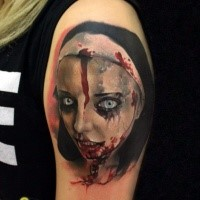 Colorful creepy looking shoulder tattoo of bloody woman