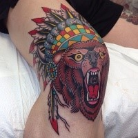Colorful old school style knee tattoo of roaring bear with Indian helmet