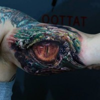 Buntes gruseliges Auge des Reptils Tattoo am Arm